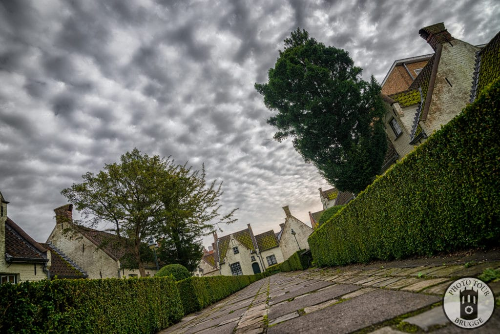 An almshouse at sunset with stunning clouds, Bruges Belgium, photo by Photo Tour Brugge.