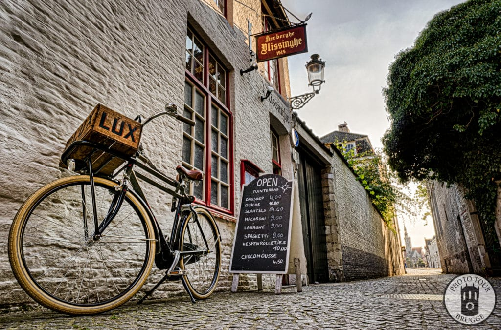 A bicycle sits by the oldest cafe in town (est 1515) at sunset on a sidestreet of Bruges Belgium. Photo by Photo Tour Brugge.