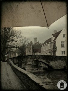 An umbrella covers from the rain on a stretch of canals in Brugge Belgium. Photo by Photo Tour Brugge.